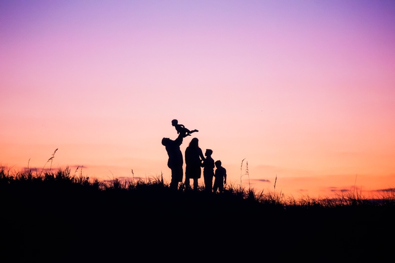 Family Photographer, family of 5 standing against a sunset