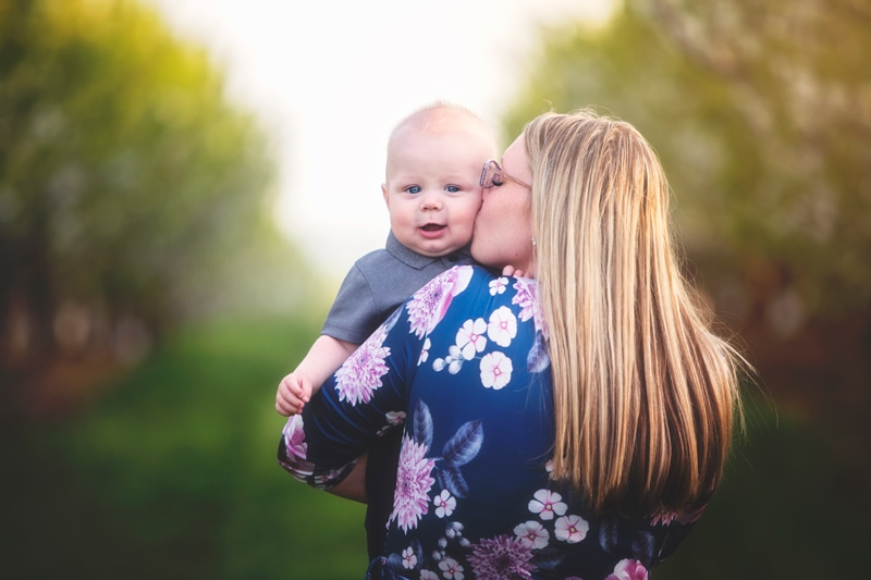 Family Photographer, mother hissing baby boy on cheek
