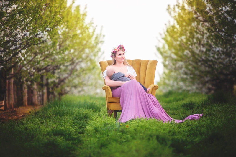 Family Photographer, mother sitting in padded chair breastfeeding little boy