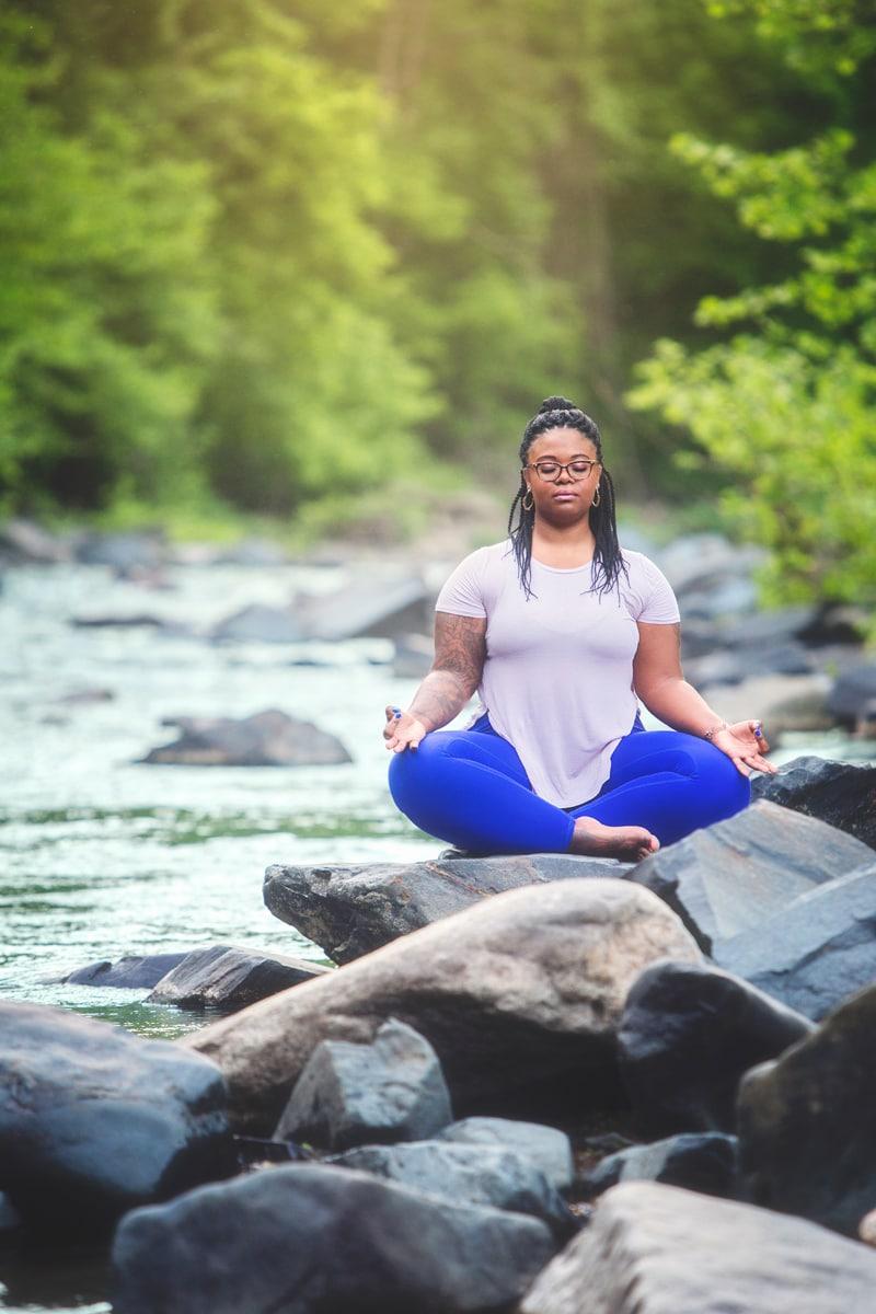 Portrait Photographer, woman meditating on rocks by the creek