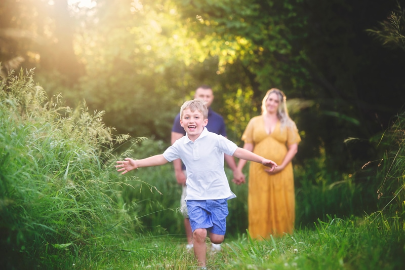 Maternity Photographer, little boy running through tall grass with mother in background