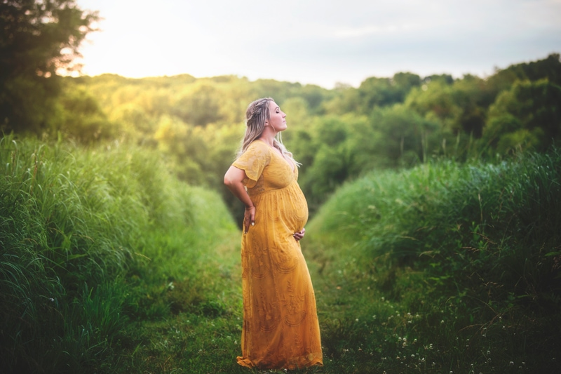 Maternity Photographer, woman in yellow dress standing with her side facing the camemra