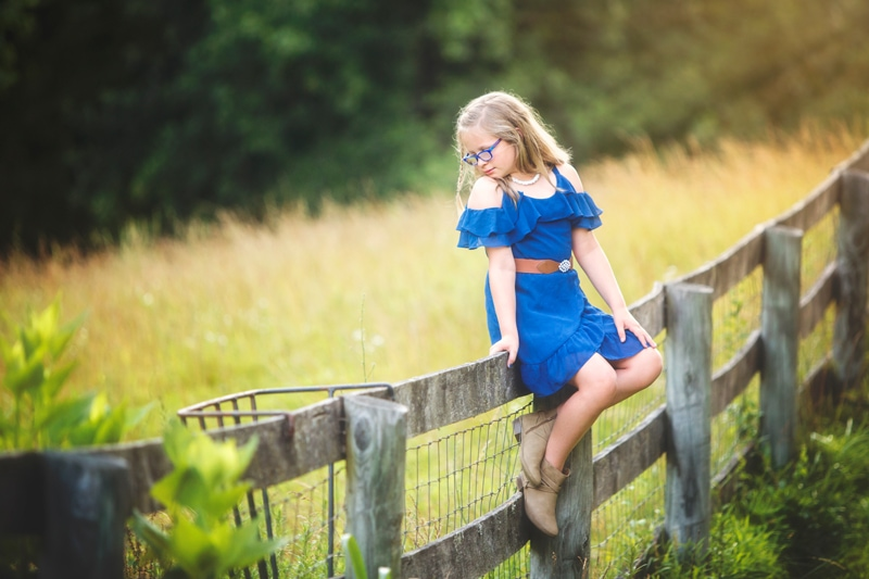 Family Photographer, little girl sitting on a wooden fence