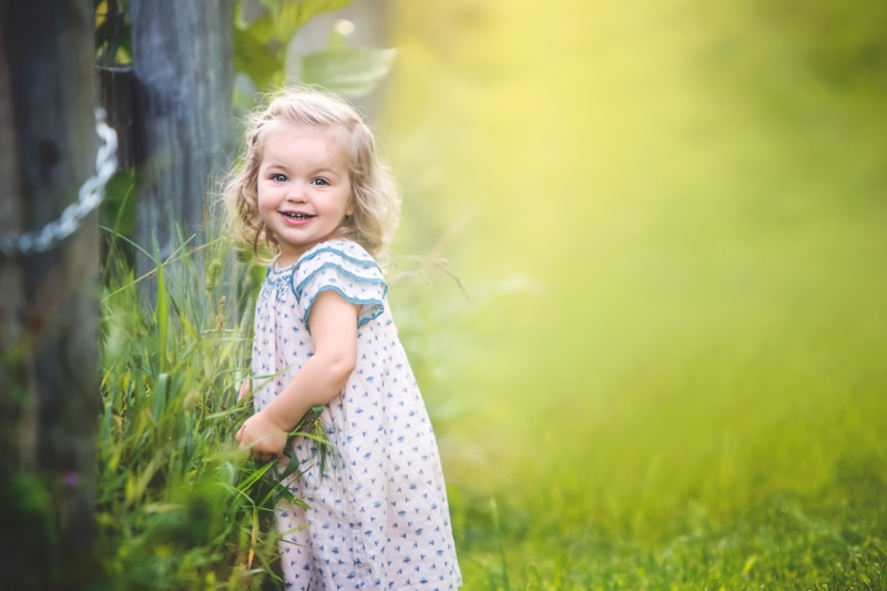 Family Photographer, little girl smiling at the camera next to a wooden fence