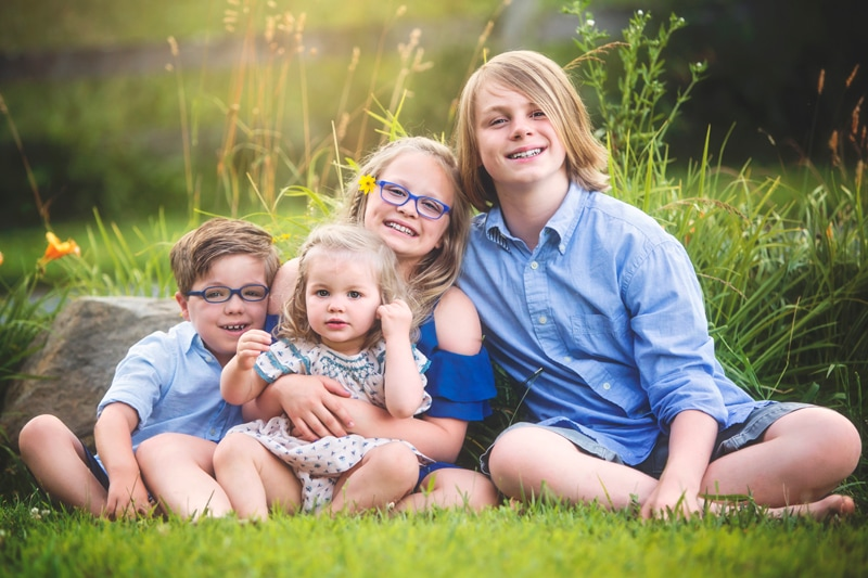 Family Photographer, 4 siblings sitting together in the grass