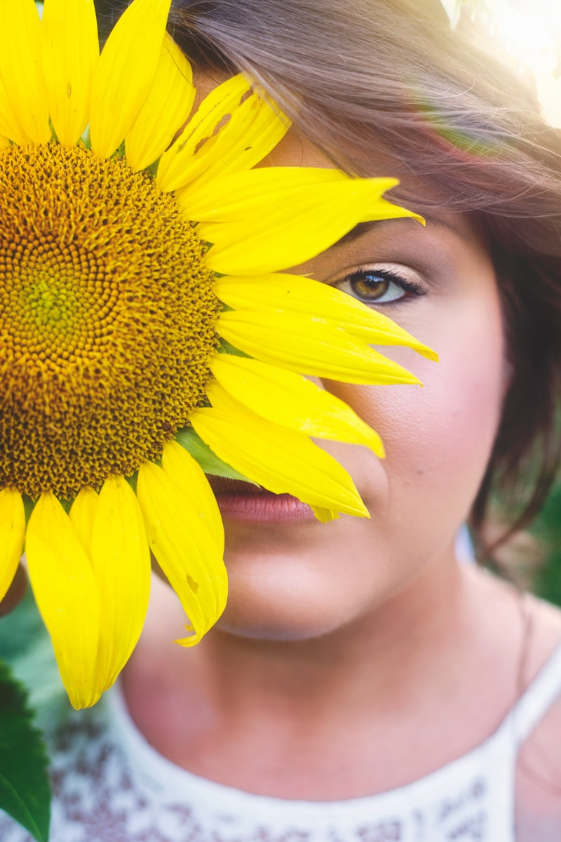 Portrait Photographer, girl with sunflower in front of her face