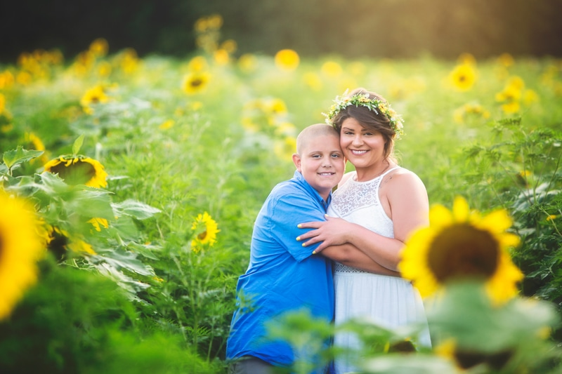 Family Photographer, young woman and young man standing in sunflowers