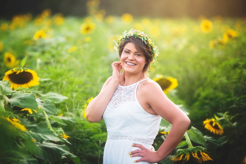 Portrait Photographer, young woman standing in a field of sunflowers
