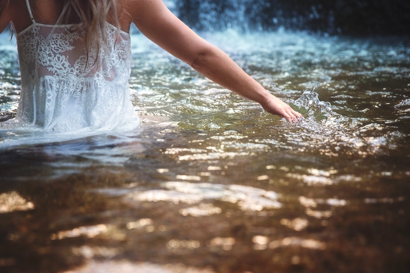 Portrait Photographer, woman running her hand across the top of water