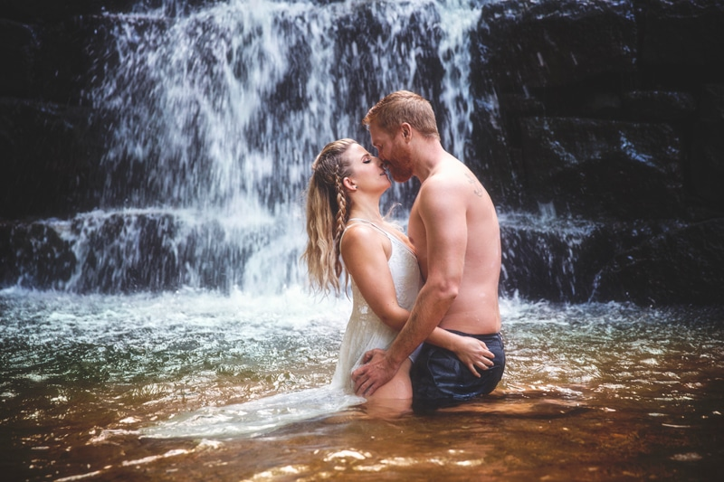 Couples Photographer, couple kissing in the water under a waterfall