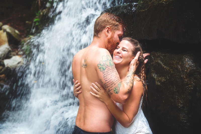 Couples Photographer, couple laughing together under a waterfall