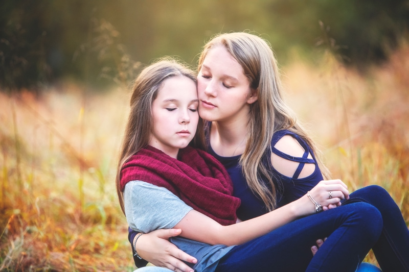 Family Photographer, daughters leaning on each other with eyes closed