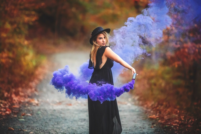 Portrait Photographer, woman twirling a smoke canister over her shoulder