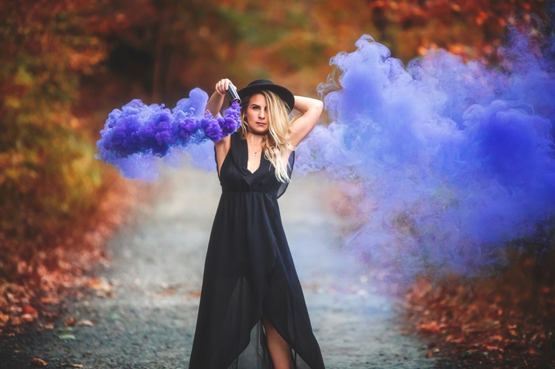 Portrait Photographer, girl in black wide-brimmed hat, twirling around a purple smoke canister