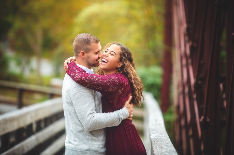 Couples Photographer, couple laughing together on bridge