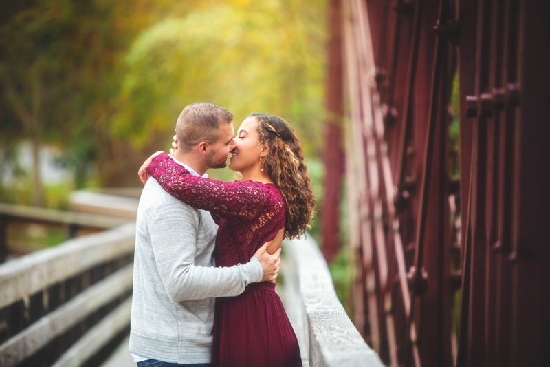 Couples Photographer, couple kissing on a bridge