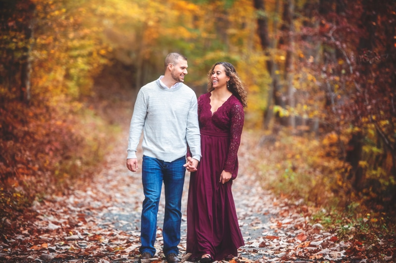 Couples Photographer, couple walking hand in hand along a dirt road
