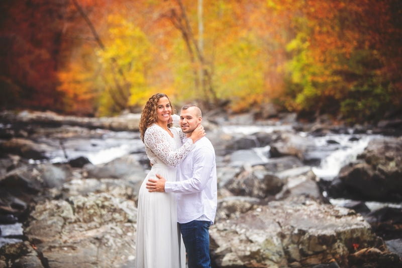 Couples Photographer, couple standing next to creek with their arms around each other